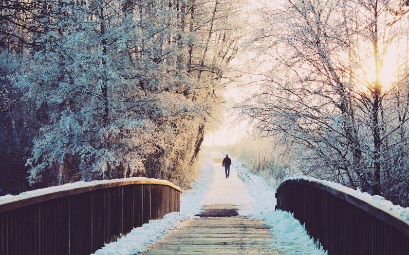 Mann geht in winterlicher Landschaft